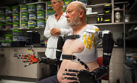 APL prosthetist Courtney Moran looks on as Les Baugh tests out the Modular Prosthetic Limbs. (Image courtesy of Johns Hopkins University Applied Physics Laboratory)