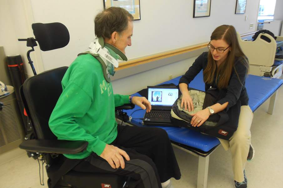 Courtney Craven, PT, DPT, provides education to a mobility device user about pressure mapping and cushion construction.